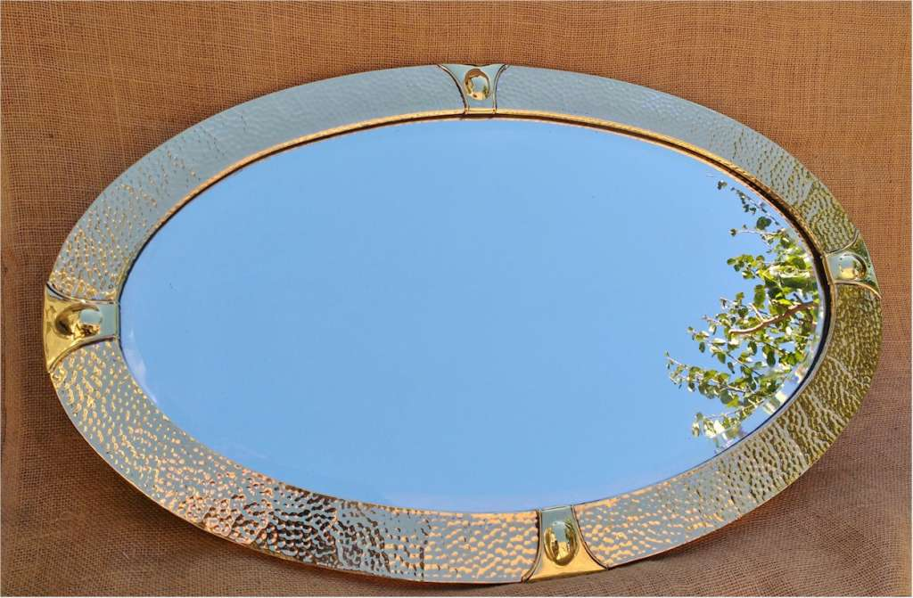 Arts and crafts mirror in hand hammered brass .