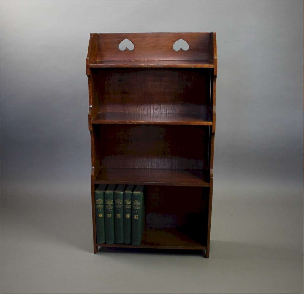 Arts and Crafts open oak bookcase with two pierced heart cut outs. c1910