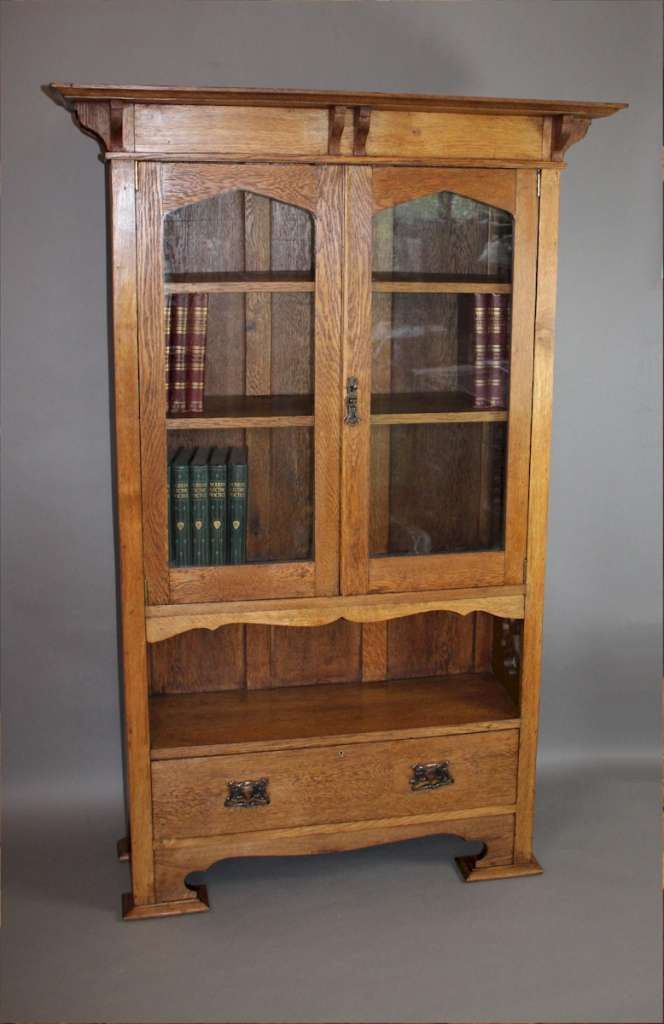 Arts and Crafts cottage oak glazed bookcase with pierced cut-outs