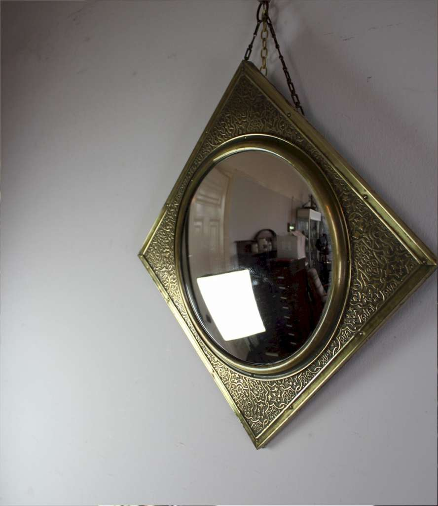 Convex mirror with chased brass frame. Early 20th century