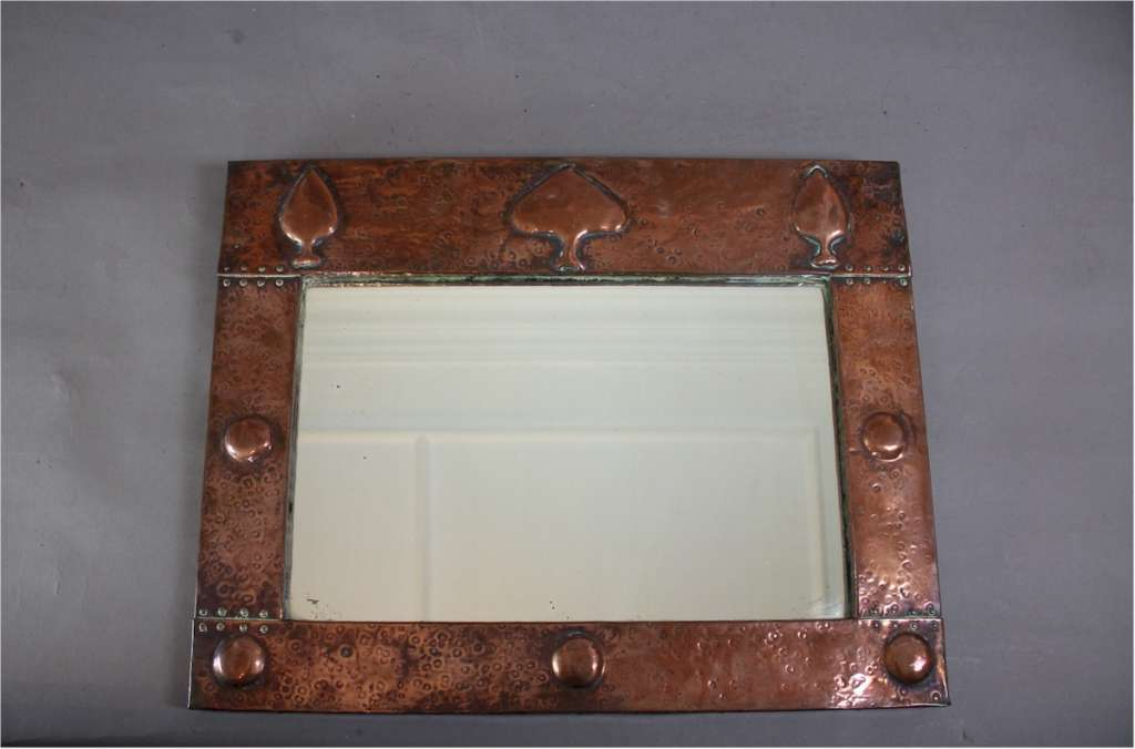 Arts and crafts copper mirror with raised spear motifs