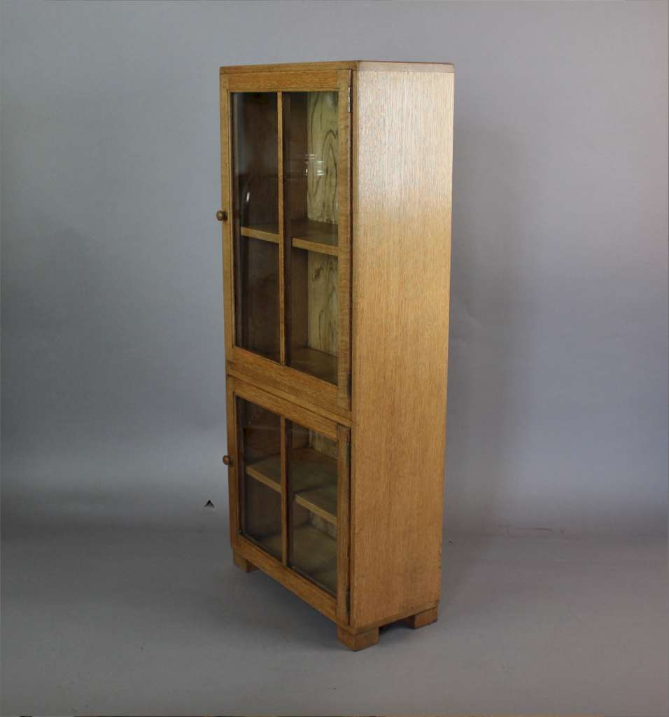 A 1930's Heals two door light oak glazed bookcase with label to door