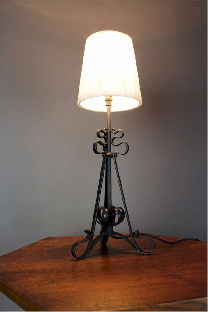 Arts and crafts iron table lamp with scrolling supports c1900