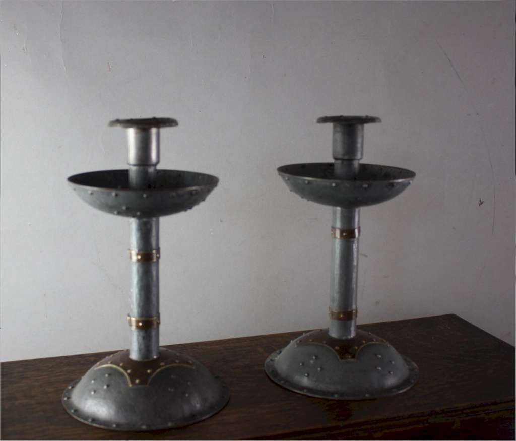 Pair of arts and crafts steel and brass candlesticks