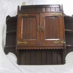Good quality arts and crafts Gothic Revival oak wall cabinet with brass hinges